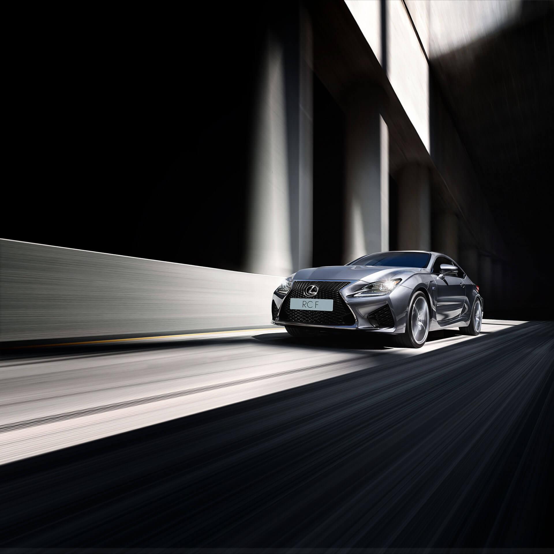 Sølvgrå Lexus RC F sportssedan selvladende hybrid kommer kjørende mot oss