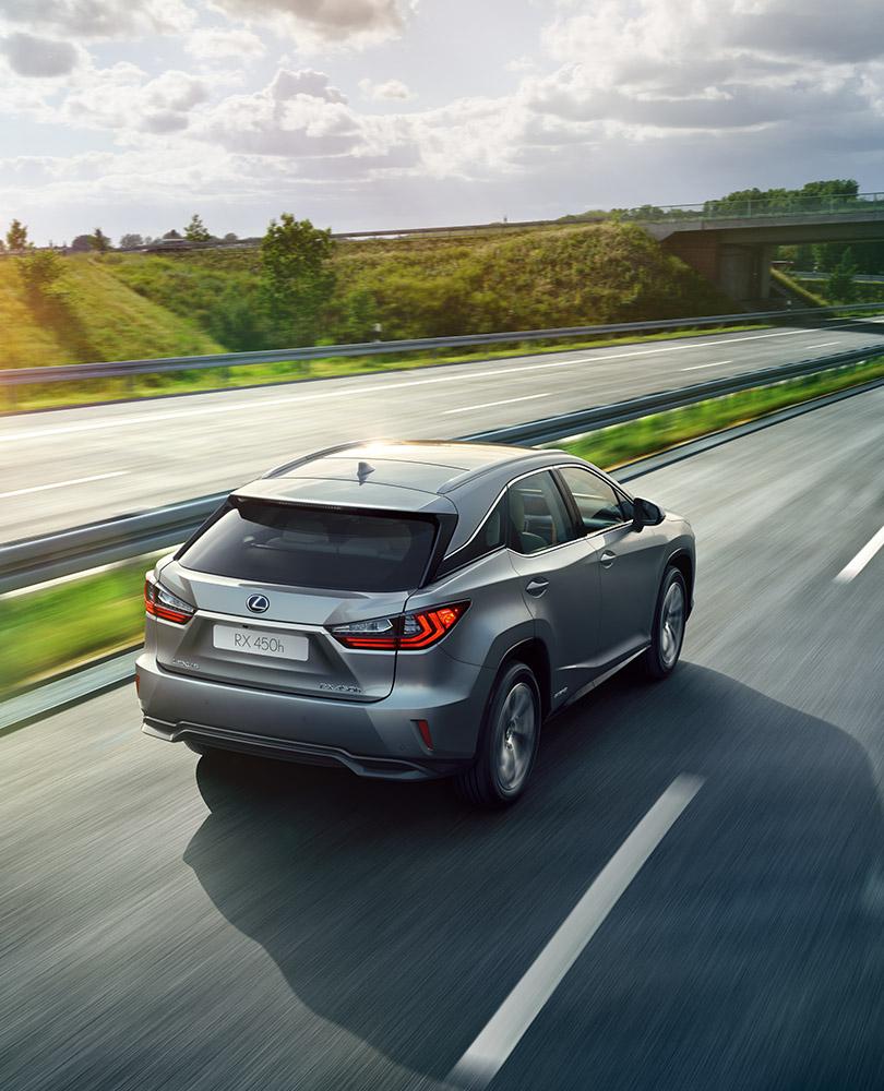 Sølvgrå Lexus SUV RX 450h selvladende hybrid kjører vekk fra oss på en motorvei