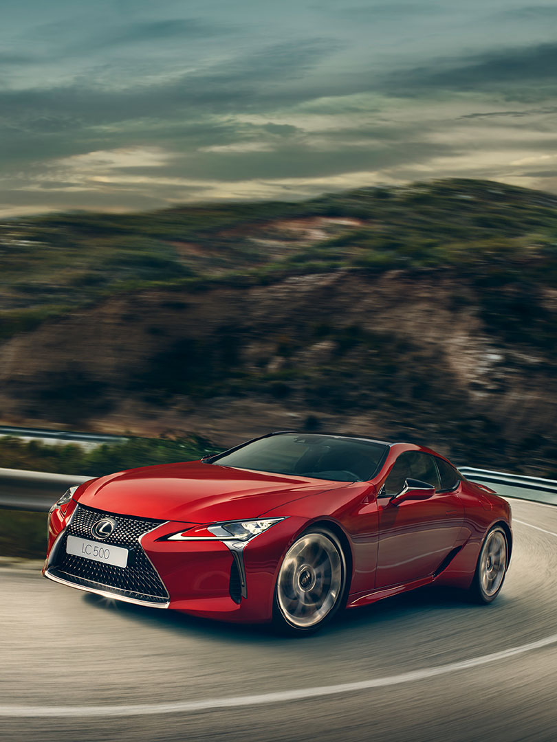 En rød Lexus LC 500h sportssedan kommer kjørende oppover i et svingete landskap